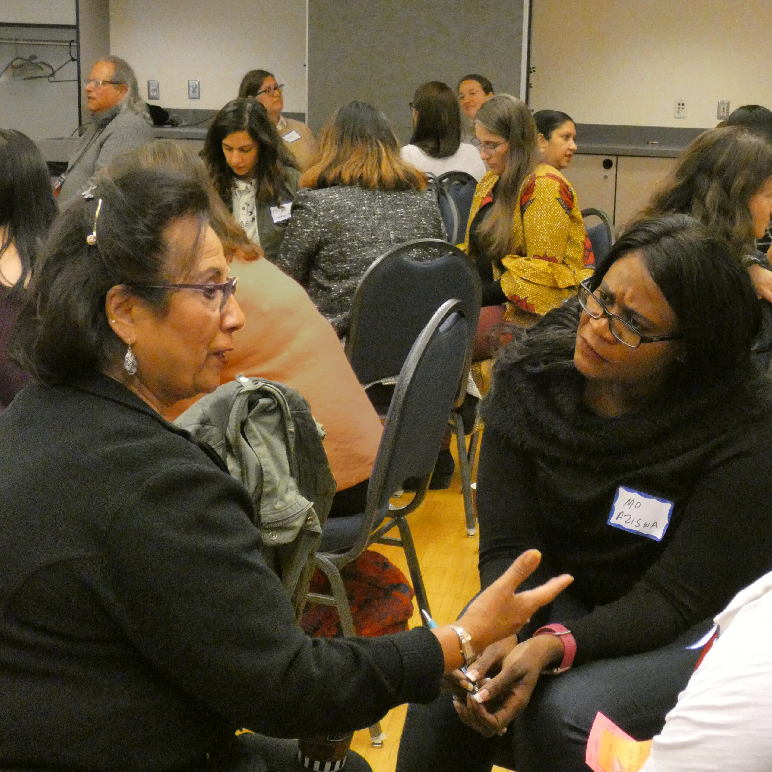 two people focusing on their conversation in a crowded room