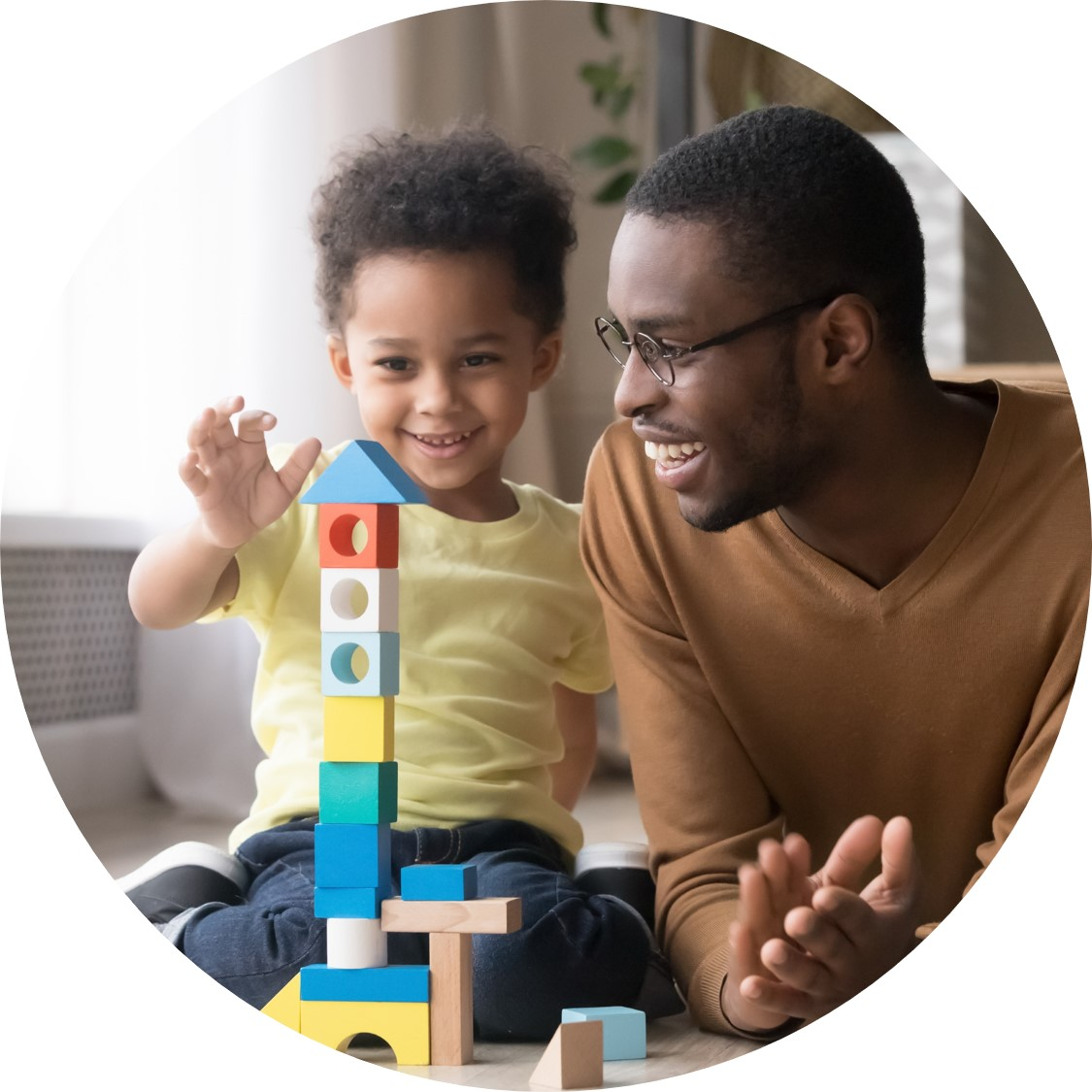 Black man smiles and claps as small Black child plays with blocks