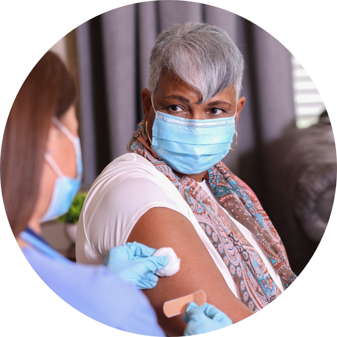 Woman with grey hair and face covering receives bandaid from nurse